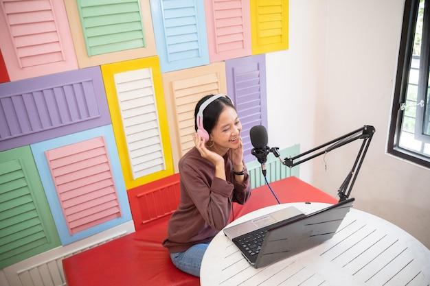 Uma garota usando um fone de ouvido na frente de um microfone durante um podcast