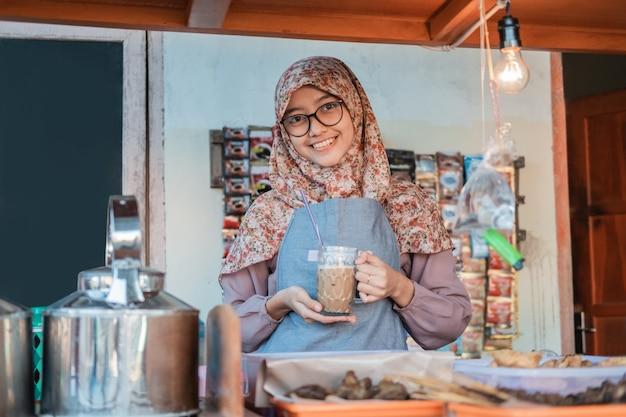 Uma garota usando um hijab em um avental sorri enquanto segura um copo de café em uma barraca de carrinho