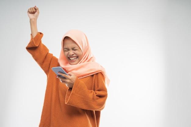Uma garota usando um véu estava segurando um celular com a mão levantada com copyspace