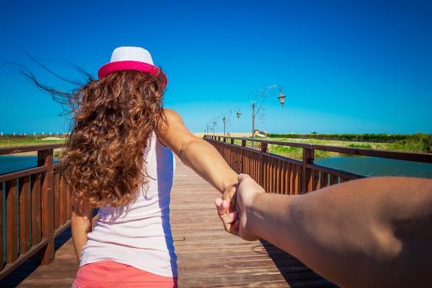 Uma garota vai em um post segurando um companheiro em uma mão
