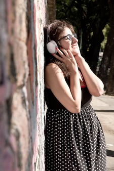 Uma garota vestida vintage listando música em um ambiente urbano.