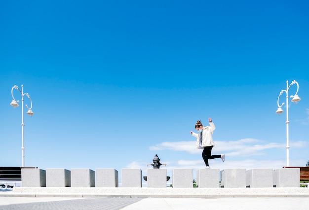 Uma garota vestindo uma máscara de segurança se diverte pulando através de um muro de concreto de uma caminhada com iluminação pública na cidade com céu azul em um dia ensolarado