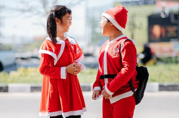 Uma garota vestindo uma roupa de areia e um garoto vestindo uma roupa de papai noel estão brincando alegremente.
