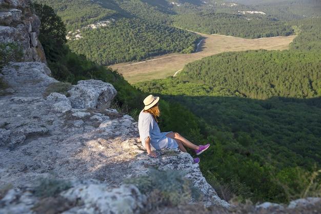 Uma garota viajante com um chapéu na cabeça dela se senta no topo de uma montanha