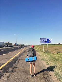 Uma garota viajante com uma mochila caminha ao longo da estrada em um dia ensolarado de verão.