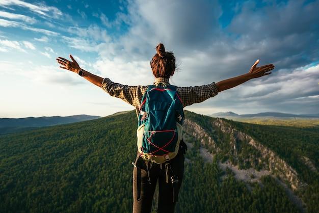 Uma garota viajante com uma mochila está de pé na beira da montanha, uma vista traseira. uma jovem com uma mochila de pé na beira de um penhasco e olhando para o céu com as mãos levantadas.