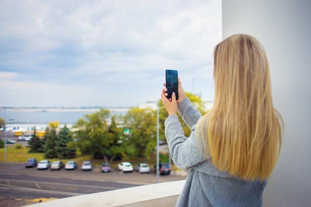 Uma garota viajante leva ao telefone uma visão geral de uma cidade grande com vista para o rio.