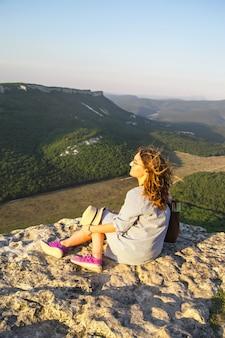 Uma garota viajante senta-se no topo de uma montanha e segura seu chapéu