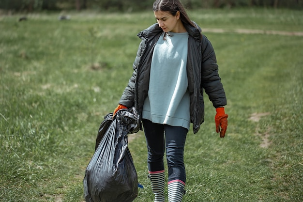 Uma garota voluntária caminha pela floresta com um saco de lixo cheio de lixo.