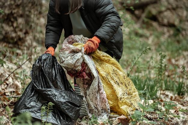 Uma garota voluntária com um saco de lixo limpa o lixo da floresta.