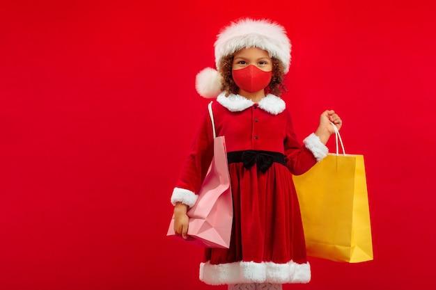 Uma garotinha afro-americana com uma máscara facial, um chapéu de papai noel e uma sacola de compras fica feliz em ir às compras antes do natal