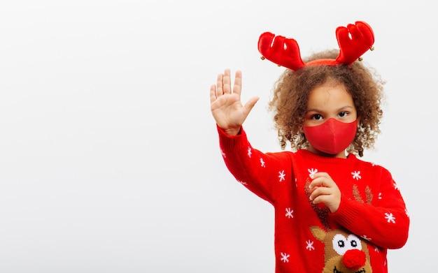 Uma garotinha afro-americana usando uma máscara facial e chifres de veado pequeno faz gestos com a palma da mão aberta, copie o espaço