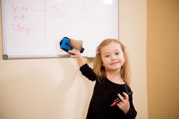 Uma garotinha ajuda um professor a limpar o quadro em uma sala de aula.
