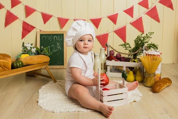 Uma garotinha alegre de boné e avental brancos sentada com frutas