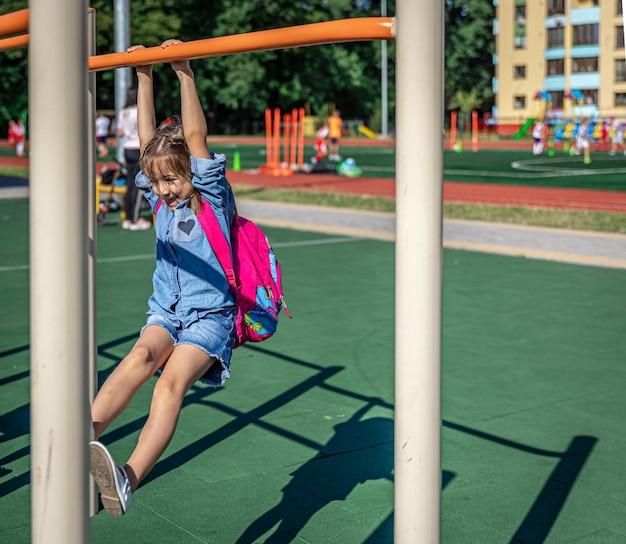 Uma garotinha, aluna do ensino fundamental, brinca no parquinho depois da escola, puxa-se para cima em uma barra horizontal.