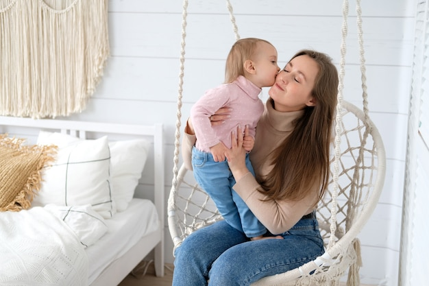 Uma garotinha beija sua mãe na cadeira de enforcamento em seu quarto brilhante quarto em estilo escandinavo