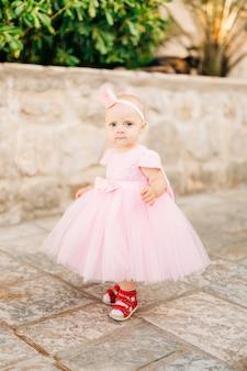 Uma garotinha charmosa de tênis rosa e uma coroa na cabeça está na estrada