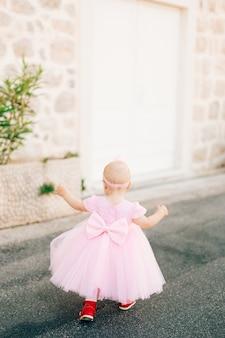 Uma garotinha charmosa em um vestido rosa com um tênis de arco e uma faixa na cabeça corre ao longo da estrada