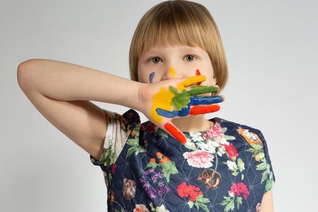 Uma garotinha cobre o rosto bonito com a mão manchada de tinta