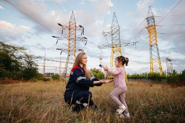 Uma garotinha coloca um capacete para sua mãe para um trabalhador de engenharia. preocupação com as gerações futuras e com o meio ambiente. energia.