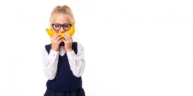 Uma garotinha com cabelos loiros enfiados no rabo de cavalo, grandes olhos azuis e um rosto bonito em óculos quadrados pretos tolos com uma banana.
