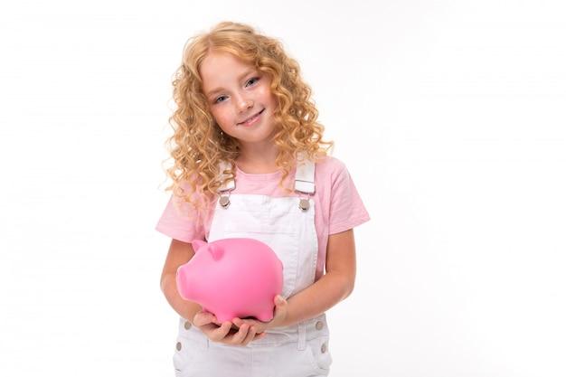 Uma garotinha com cabelos vermelhos em uma camisa, macacão branco e tênis branco com um cofrinho rosa.