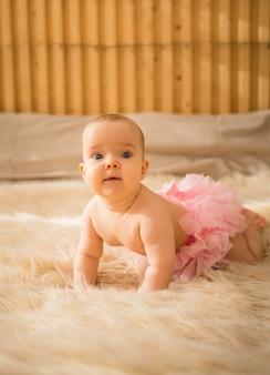 Uma garotinha com calcinha de babado rosa engatinha em um cobertor de pele no quarto
