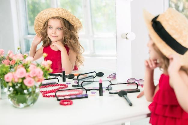 Uma garotinha com cosméticos. ela está no quarto da mãe, sentada perto do espelho.