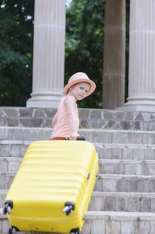 Uma garotinha com ondas de luz entende os degraus de uma grande mala amarela. uma criança linda com um chapéu de palha.