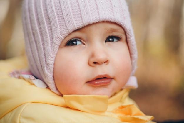 Uma garotinha com um chapéu quente na cabeça sorriu.