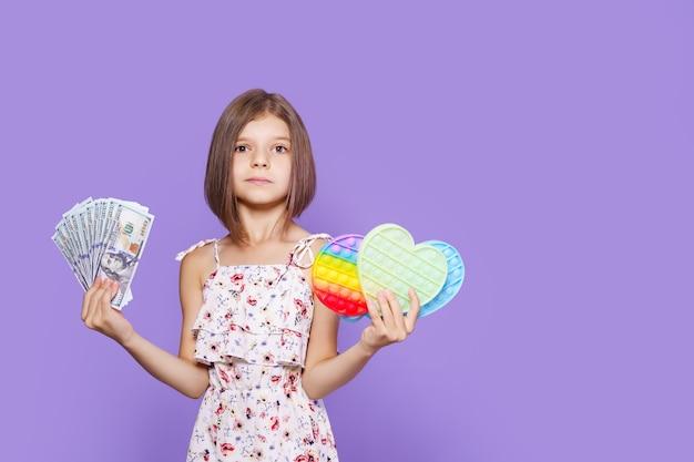 Uma garotinha com um vestido de verão segura em uma das mãos e com dinheiro em dólares na outra e olhando para ...