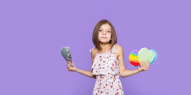 Uma garotinha com um vestido de verão segura em uma das mãos o dinheiro em dólares na outra e pensa