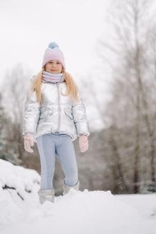Uma garotinha com uma jaqueta prateada no inverno sai de casa no inverno.