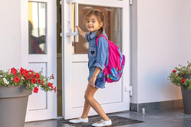 Uma garotinha com uma mochila, uma colegial abre as portas da escola.