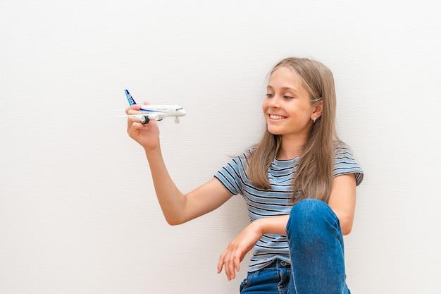 Uma garotinha de jeans está sentada no chão em uma sala e brincando com um avião