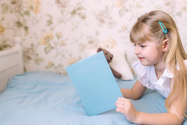 Uma garotinha deita na cama no quarto elegante e lê um livro azul, fazendo o dever de casa