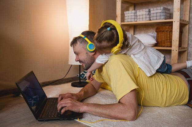 Uma garotinha deita-se nas costas do pai e ouve música com fones de ouvido amarelos enquanto olha para seu laptop. o conceito de felicidade familiar