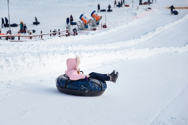 Uma garotinha desce um escorregador em um tubo