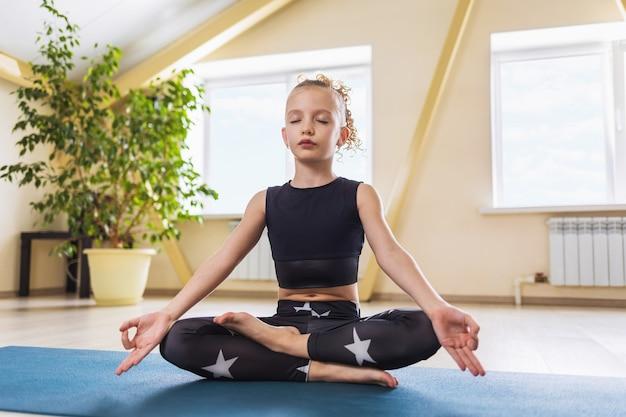 Uma garotinha em roupas esportivas praticando ioga está envolvida em meditação sentada em posição de lótus na sala