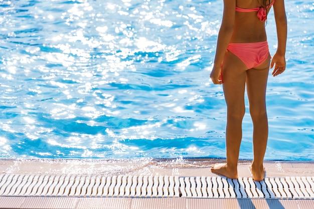 Uma garotinha em um maiô brilhante está de pé perto de uma grande piscina e olha para a água límpida e transparente, se preparando para pular nas tão esperadas férias de verão