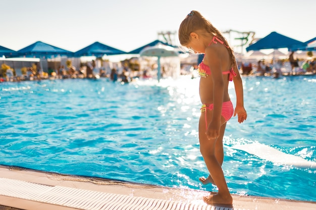 Uma garotinha em um maiô rosa choque está ao lado da piscina com água transparente e limpa e tenta com o pé