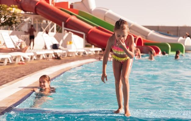 Uma garotinha em um maiô rosa choque está ao lado da piscina com água transparente e tenta com o pé