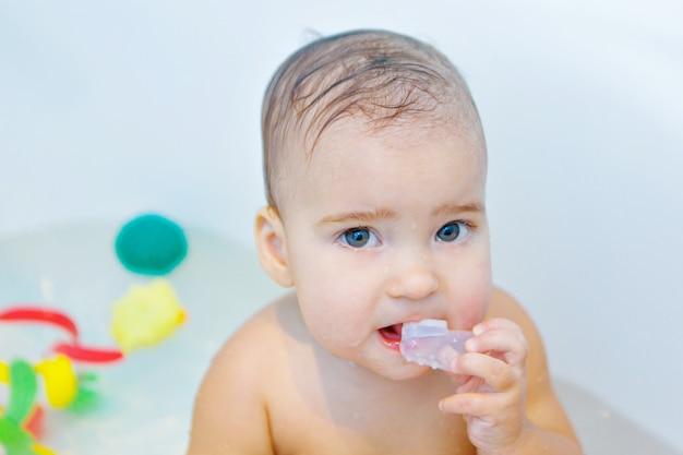 Uma garotinha escova os dentes no banheiro. retrato de uma criança com uma escova de dentes