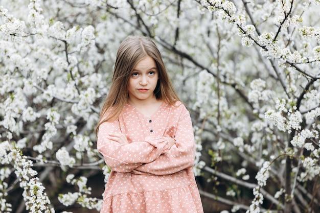 Uma garotinha está de pé com os braços cruzados sobre o peito e parece com uma expressão de satisfação no rosto.