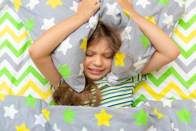 Uma garotinha está deitada na cama e é safada, não quer ir à escola.