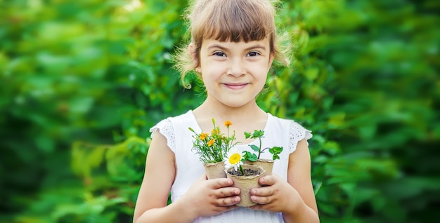 Uma garotinha está plantando flores
