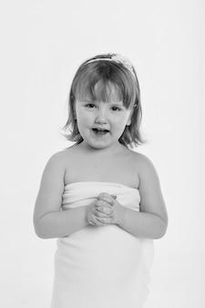 Uma garotinha faz uma careta. a criança está tramando algo. conceito de emoções, expressões faciais, infância, sinceridade