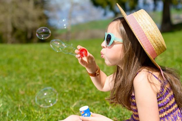 Uma garotinha fazendo bolhas de sabão