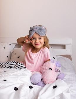 Uma garotinha loira de pijama e máscara de dormir está sentada na cama com um brinquedo macio
