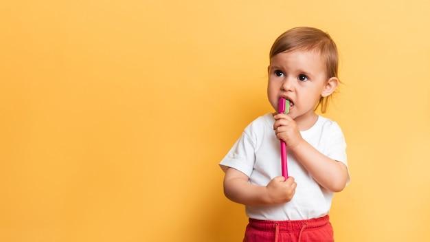 Uma garotinha loira escova os dentes com pasta de dente. fundo amarelo. um lugar para o seu texto. o conceito de higiene dental.